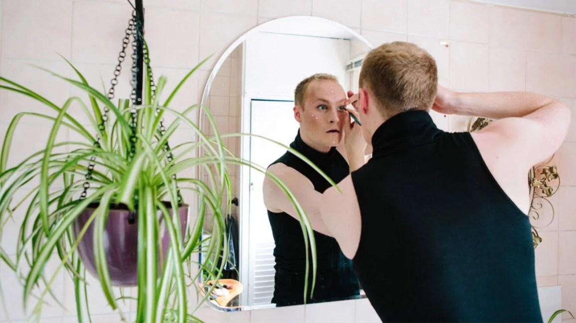 pessoa com cabelo loiro bagunçado aplicando delineador preto no espelho