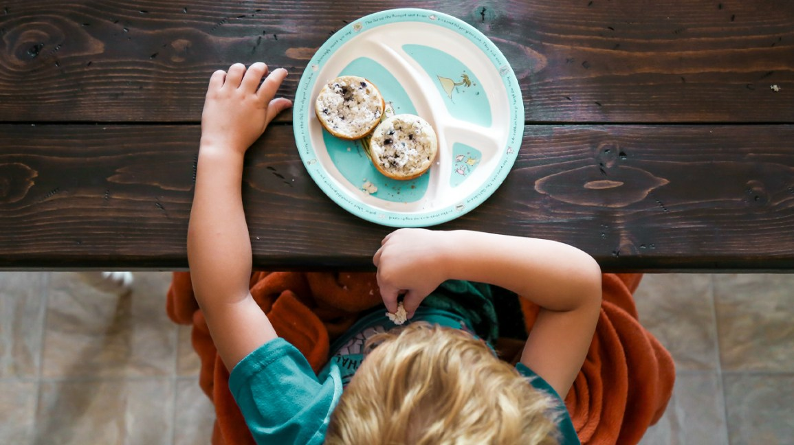 Child sits at table and eats breakfast off plate