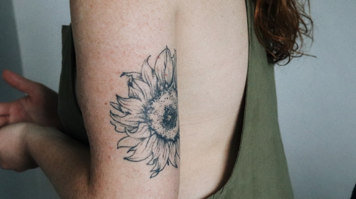 sunflower tattoo on the back of the upper arm of a woman