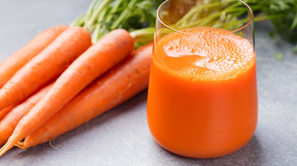 a glass of carrot juice beside carrots