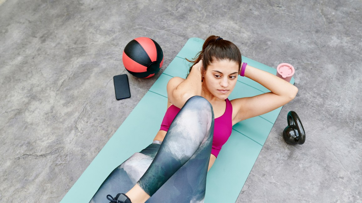 A woman lies on an exercise mat while doing bicycle crunches as part of an EMOM workout.