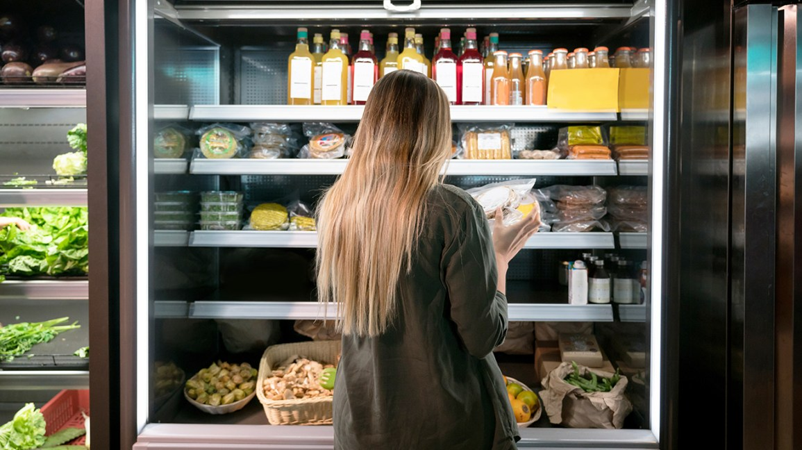 Woman looking at the nutrition facts label of a product in a supermarket
