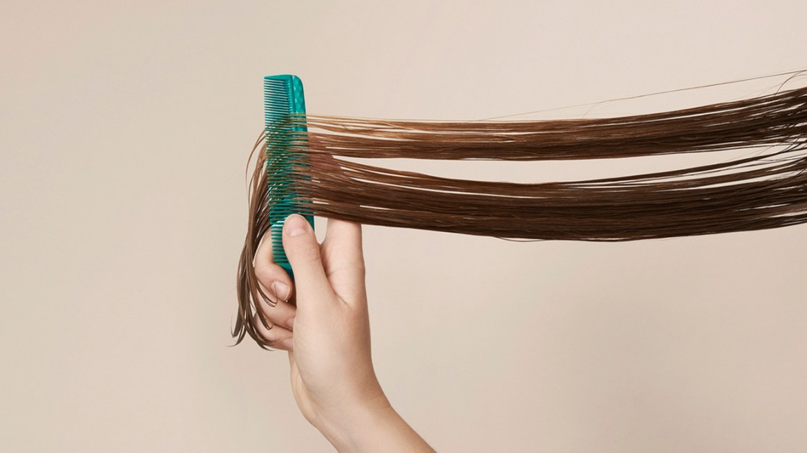 Strands of long hair with a comb brushing through the strands.