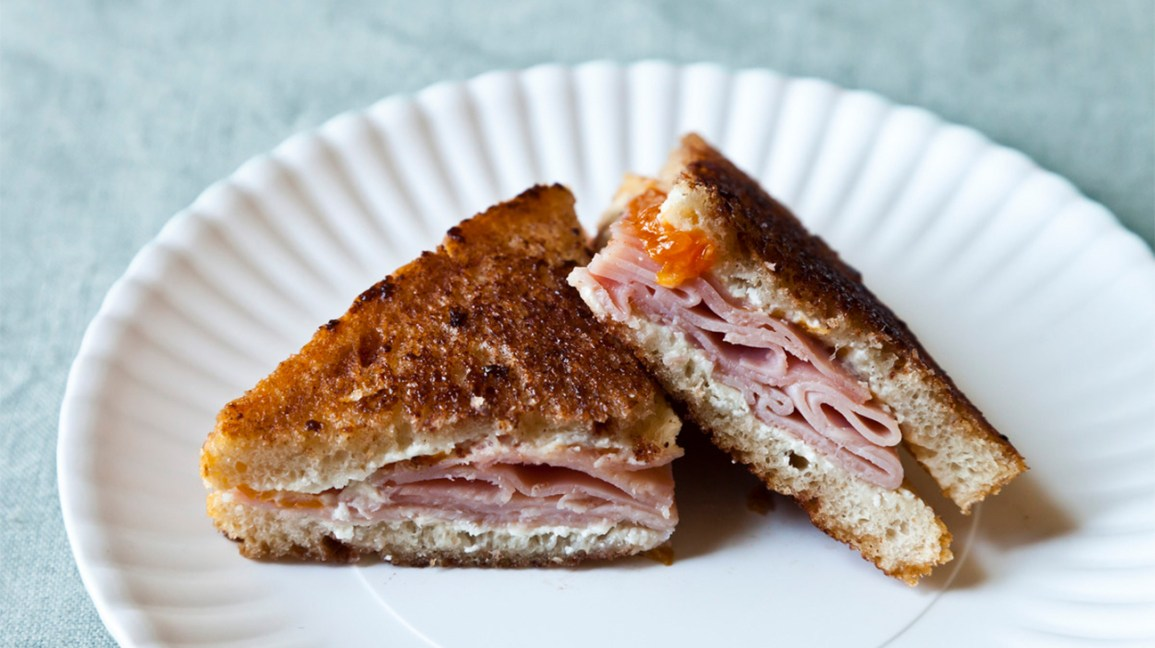 grilled ham sandwich on a paper plate