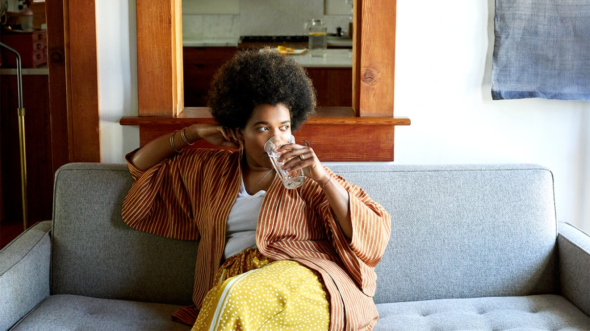a woman drinking a glass of water on a couch