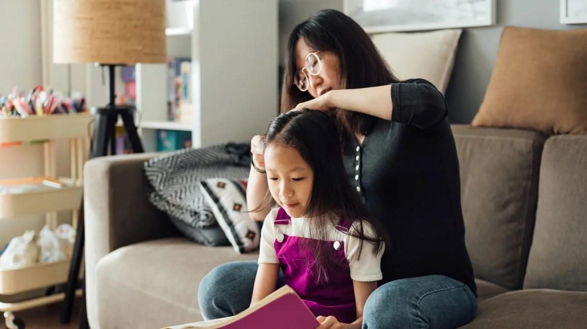 Mãe escovando o cabelo da filha