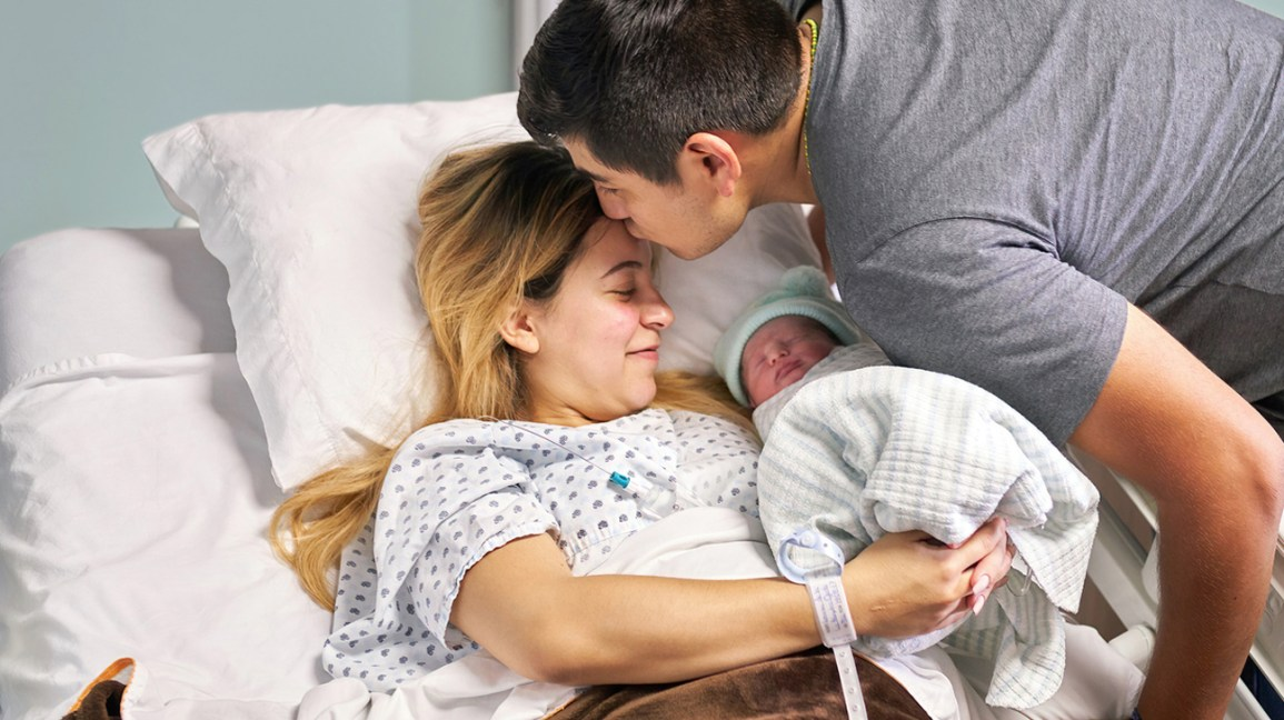 Pais segurando recém-nascido no hospital