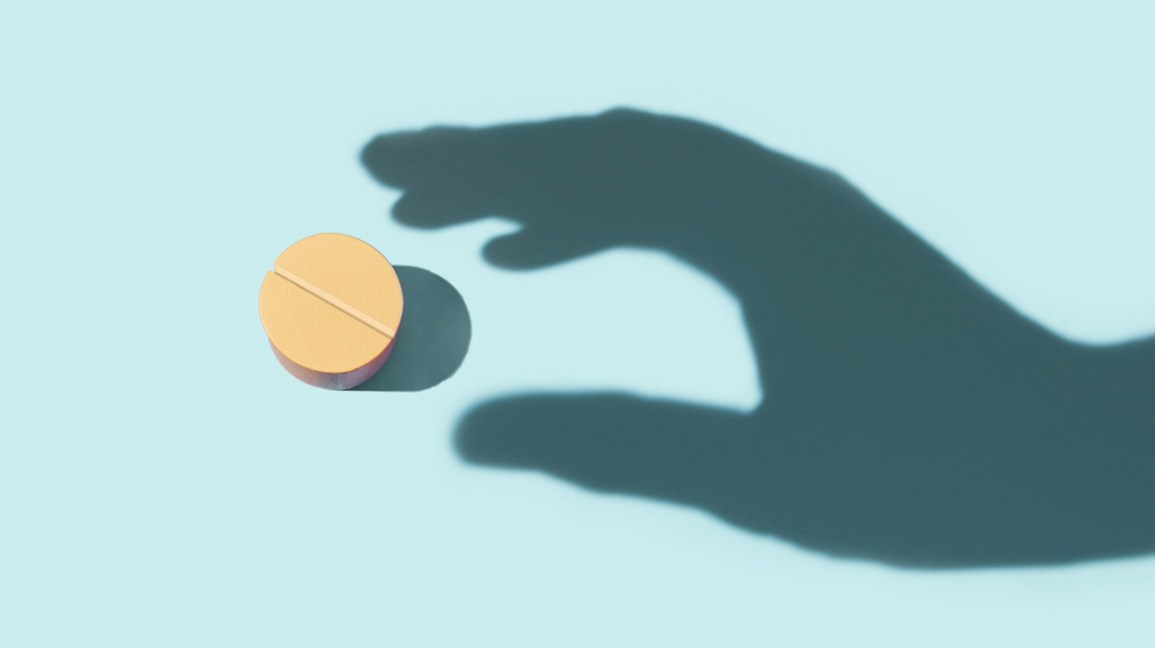Shadow of hand reaching for pill