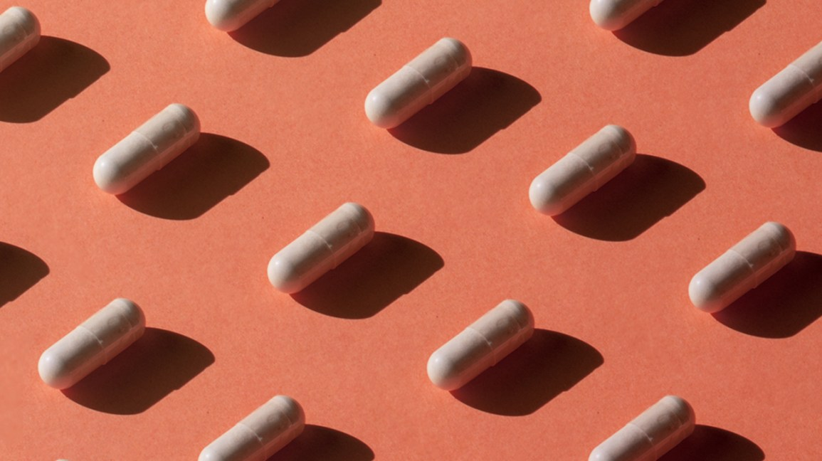 pattern of white probiotic supplements in front of a solid peach background