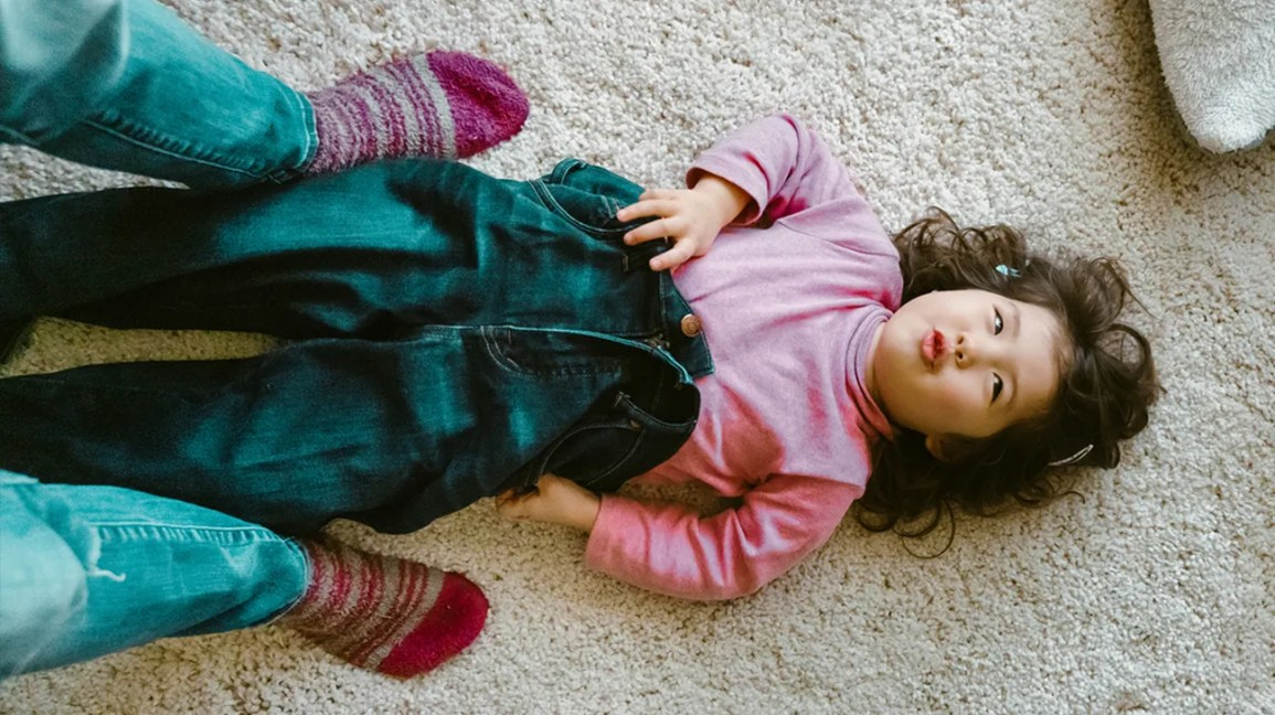 child playing dress up in parent's jeans