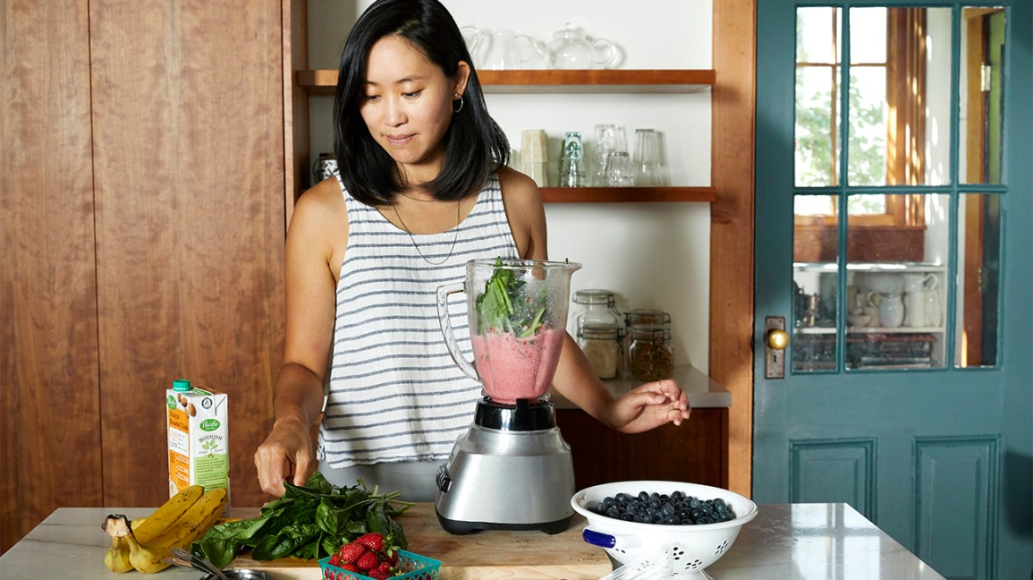 woman making smoothie with fresh and frozen fruits and vegetables