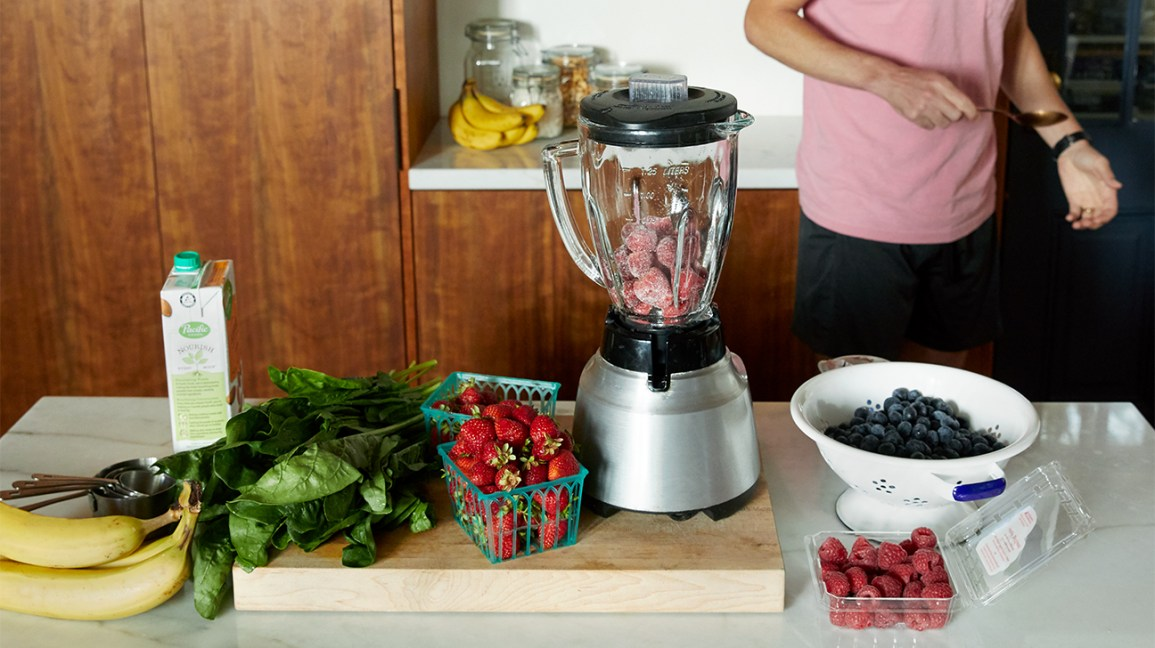 bananas, spinach and berries on a counter with a blender