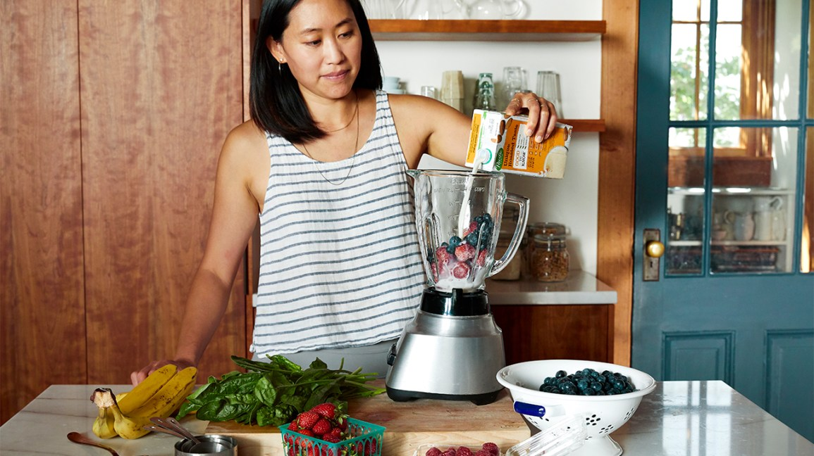 woman making a smoothie with frozen and fresh fruit and veggies