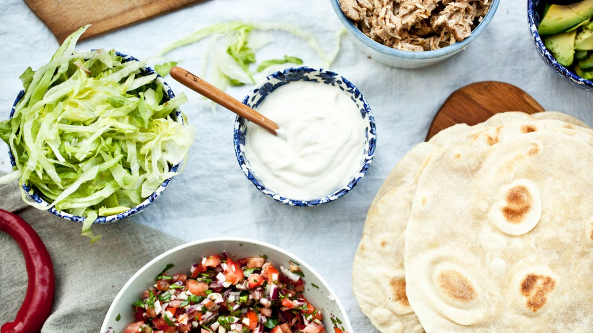 a bowl of sour cream with various taco fixings