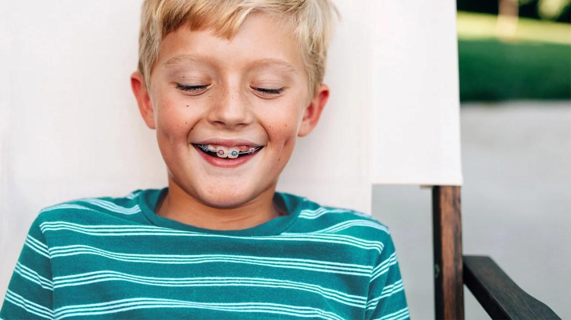 anak laki-laki dengan kawat gigi dan bumper bibir