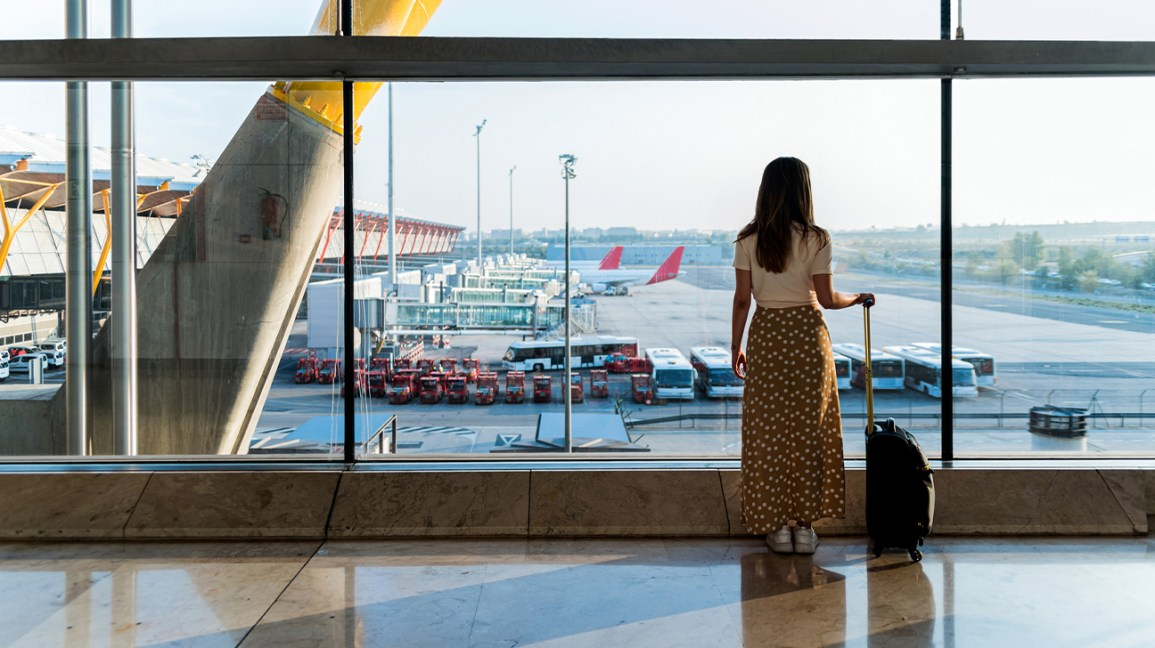 A woman stands at a window at an airport getting ready to board a flight.
