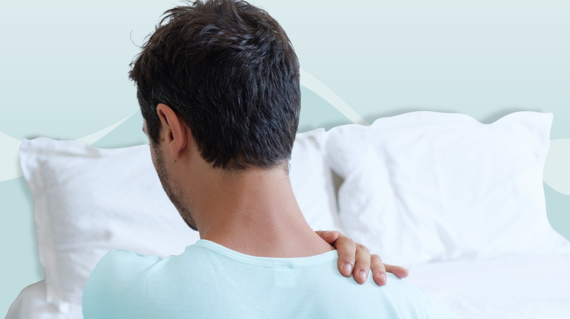 Man holding his shoulder in bed