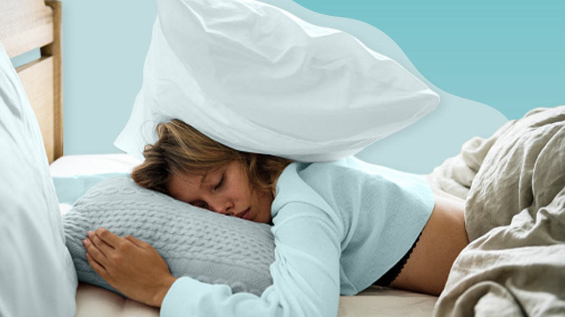 woman sleeping on a mattress with a pillow over her head