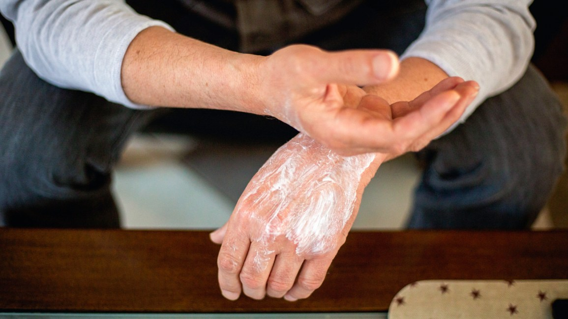 Rubbing ointment on hands