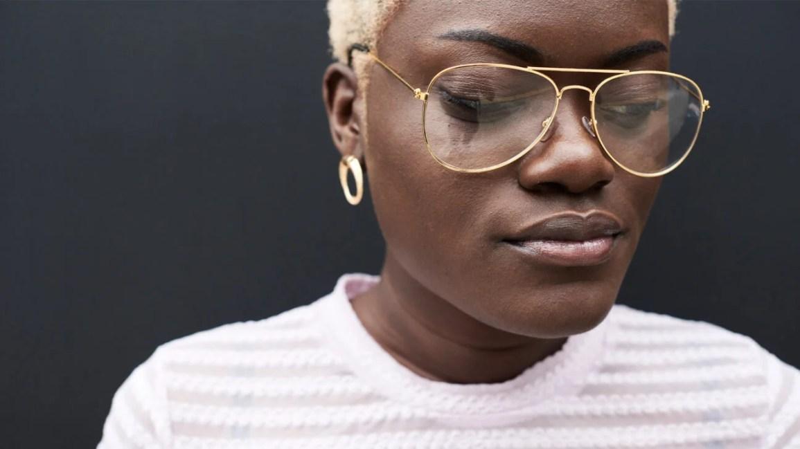 closeup retrato de mulher negra com blong curto e óculos de ouro