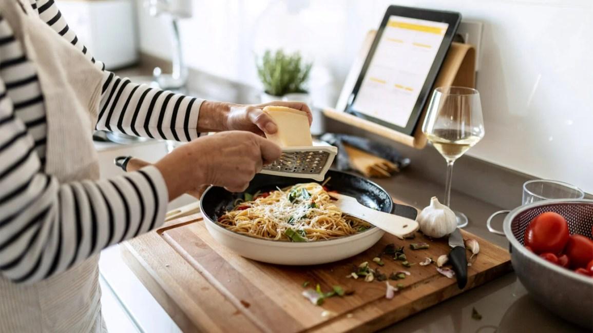 Uma pessoa na cozinha rala queijo em uma panela de Teflon que contém espaguete.