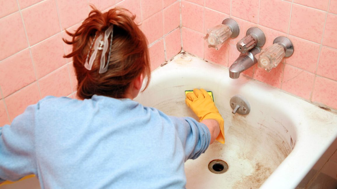 does hydrogen peroxide kill mold, woman scrubbing a bathtub