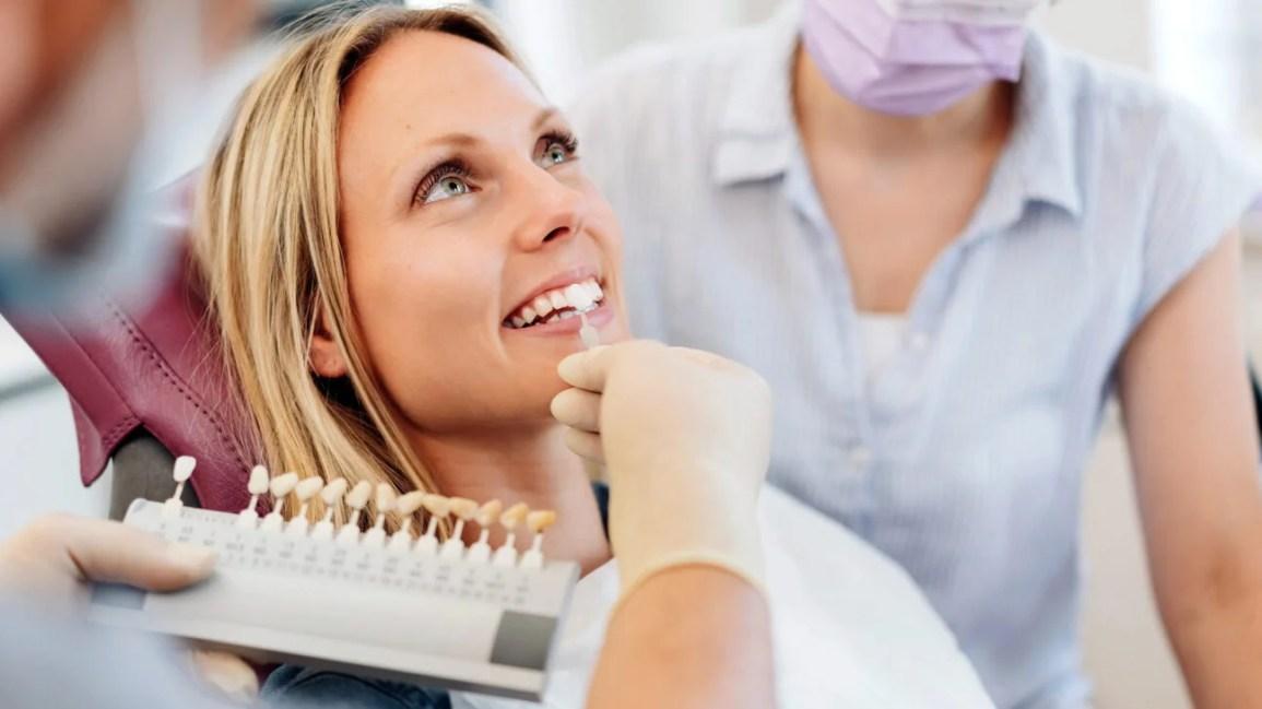 Um dentista mostra as opções de verniz a um paciente na cadeira do dentista.