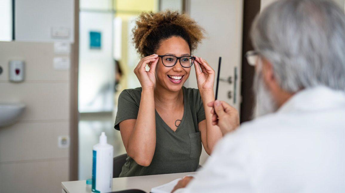 Bir kadın bir çift gözlük deniyor.