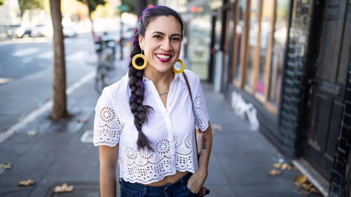 similing woman with long braid smiling on sidewalk