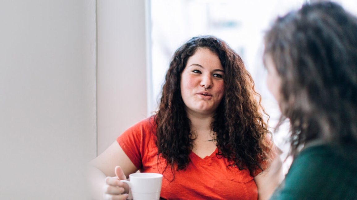woman wearing red shirt and holding coffee cup in mid-conversation
