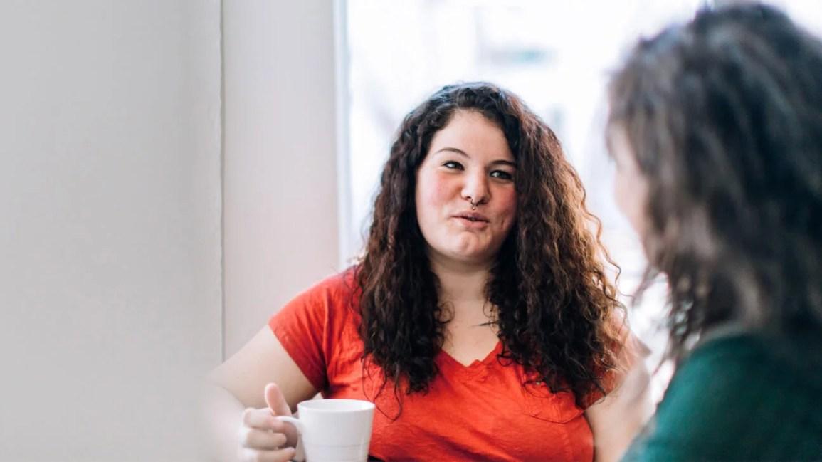 mulher de camisa vermelha segurando uma xícara de café no meio de uma conversa