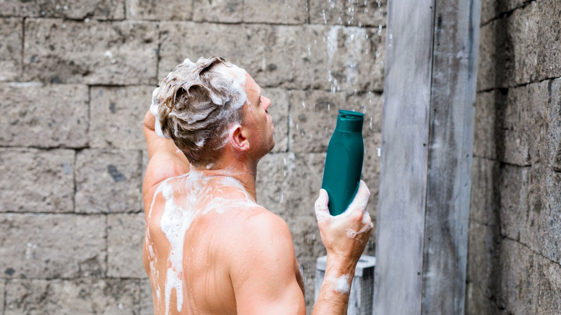 A man stands in the shower while washing his hair with shampoo.