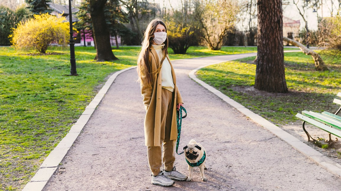 A girl wearing a face mask stands in a park with her dog on a leash.