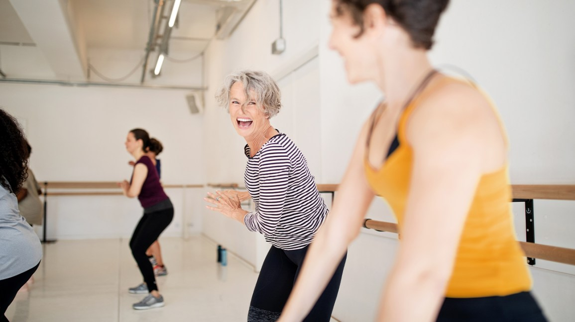Women in a dance class laugh while they do dance moves.