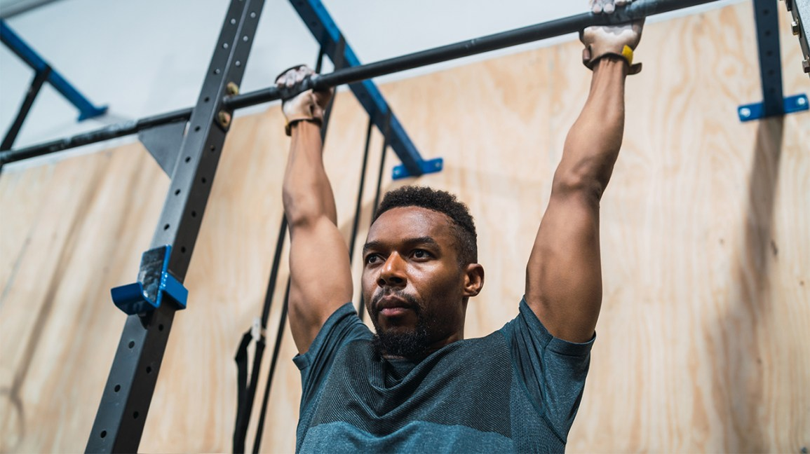 Person preparing for a pull-up at the gym