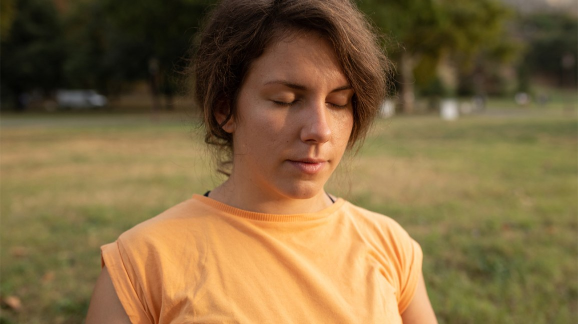 woman in orange shirt meditating outside