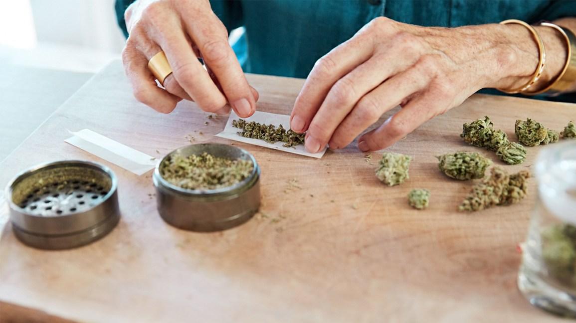 close-up de duas mãos enrolando um baseado de cannabis com um moedor