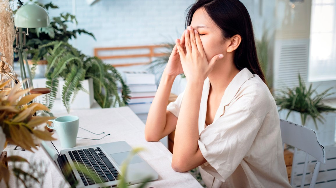 cybersickness, woman feeling unwell while sitting at a desk