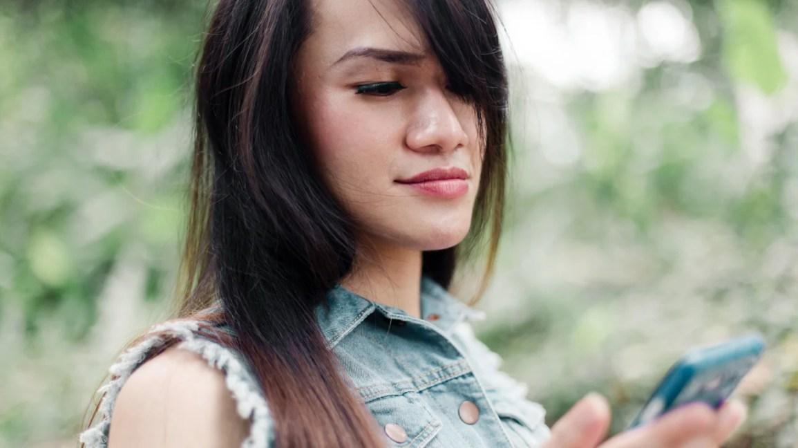 uzun kahverengi saçlı, kanatlı göz kalemi ve telefonuna bakarken kot yeleği olan transfeminine bir kişinin kırpılmış portresi