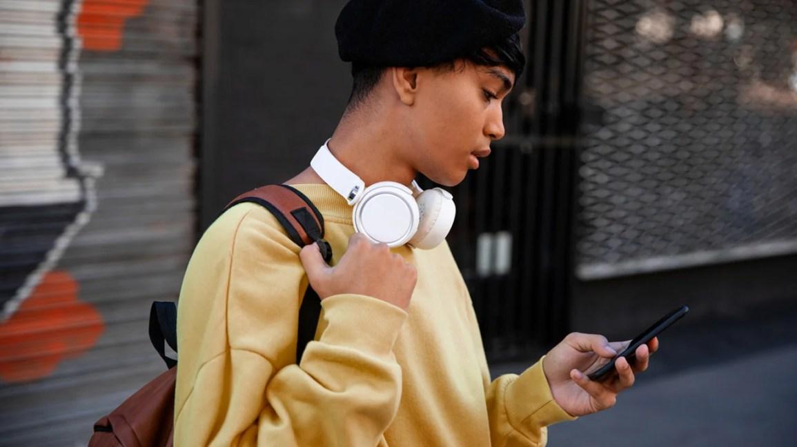 retrato recortado de uma pessoa transmasculina com cabelo preto curto preso sob uma boina azul-marinho, fones de ouvido brancos no pescoço e um moletom amarelo olhando para o telefone