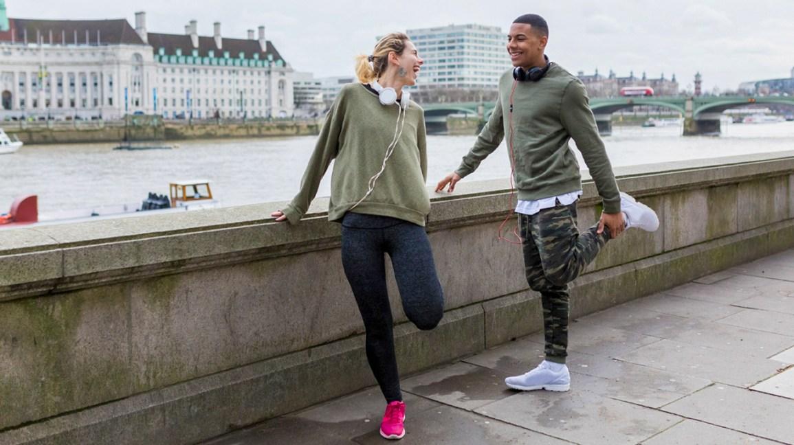 Duas pessoas, em um ambiente urbano, alongam seus quadríceps após o treino.