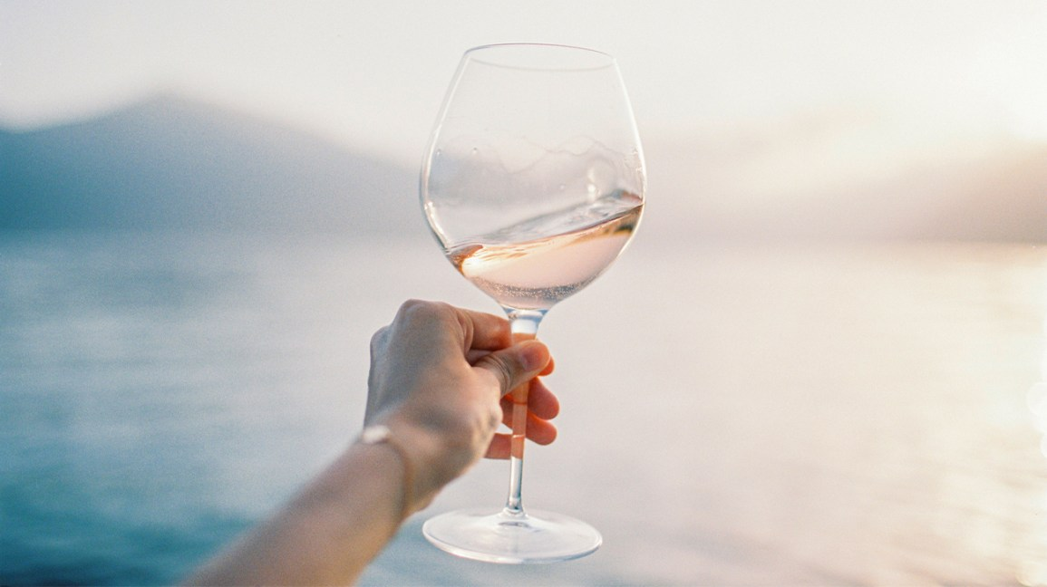 hand holding the stem of a large wine glass in front of body of water