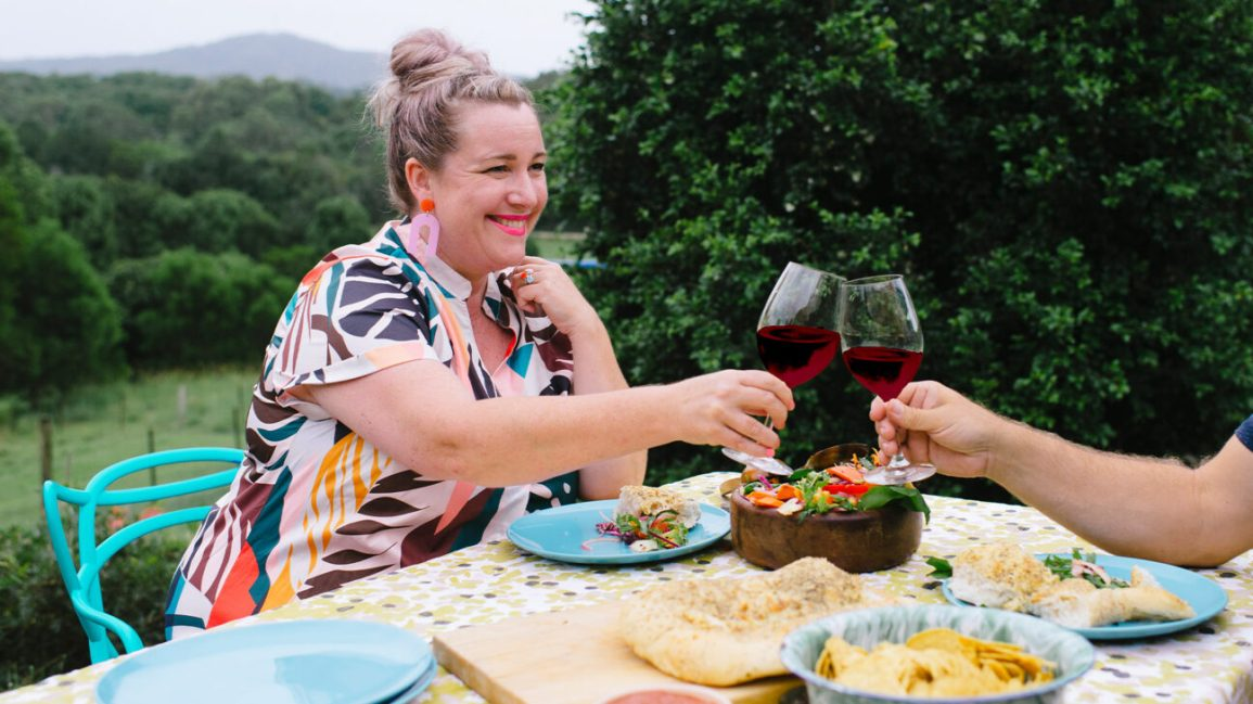 Woman toasting with wine glass at outdoor picnic table