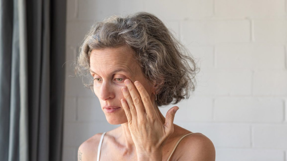 A woman touches the outer corner of her left eye with her fingers.