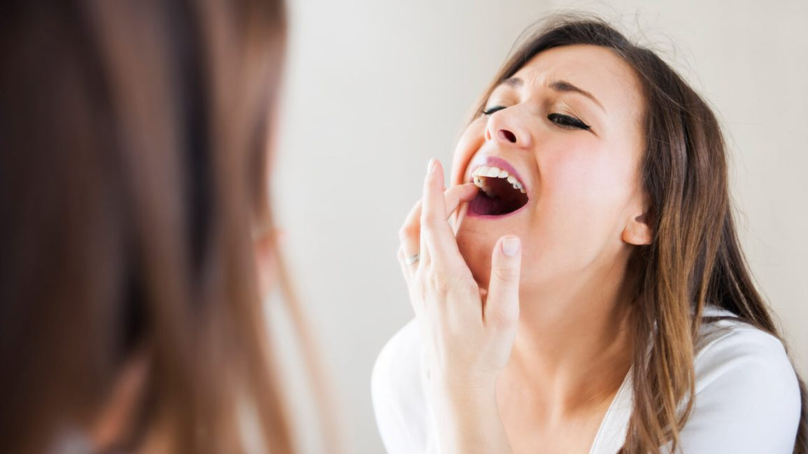 A woman stands in front of a mirror checking out a dark dot on her tooth.