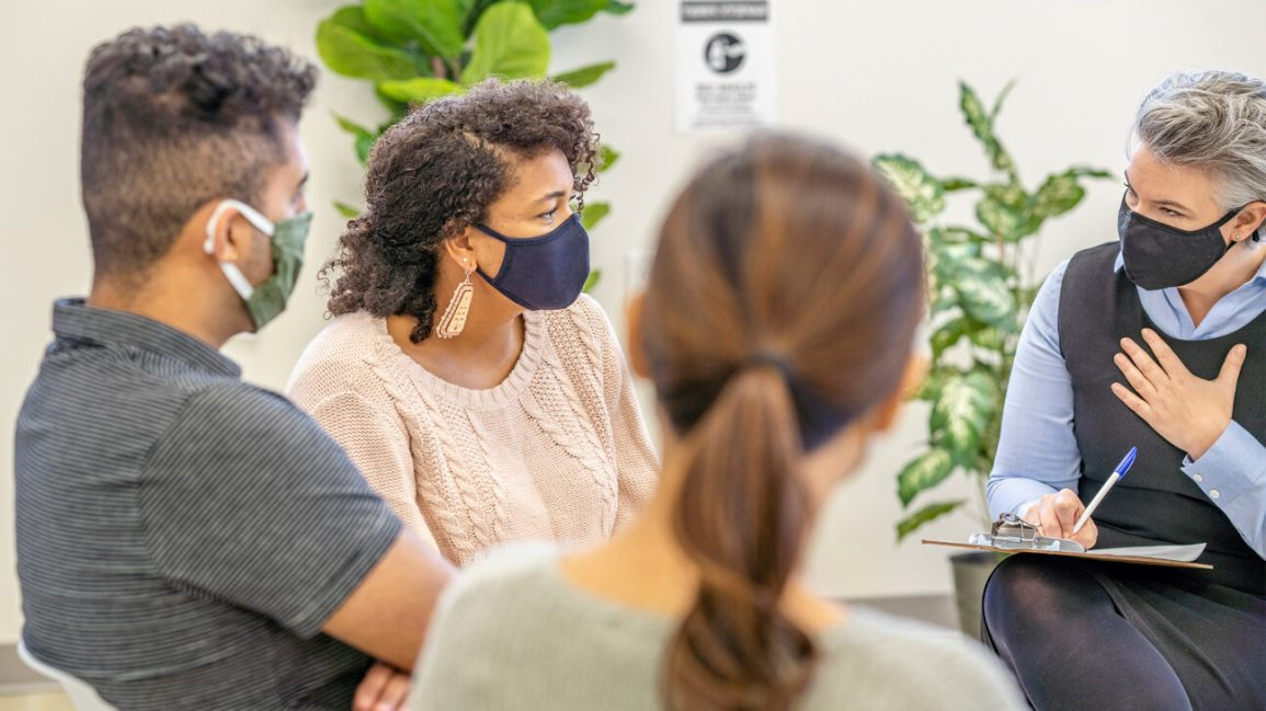 pessoas sentadas em terapia de grupo usando máscaras