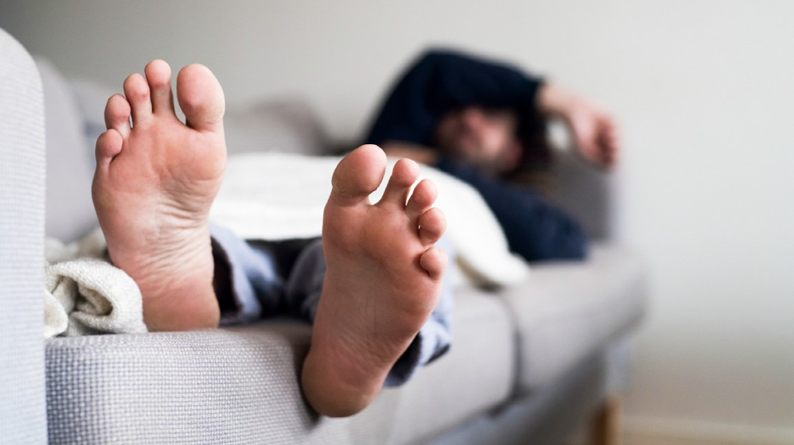A person lies asleep on a bed, with their feet sticking out from under the covers.