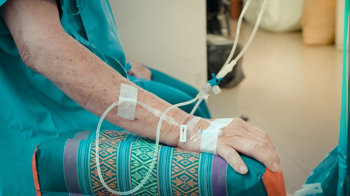 A woman sits in a chair with an IV in her arm.