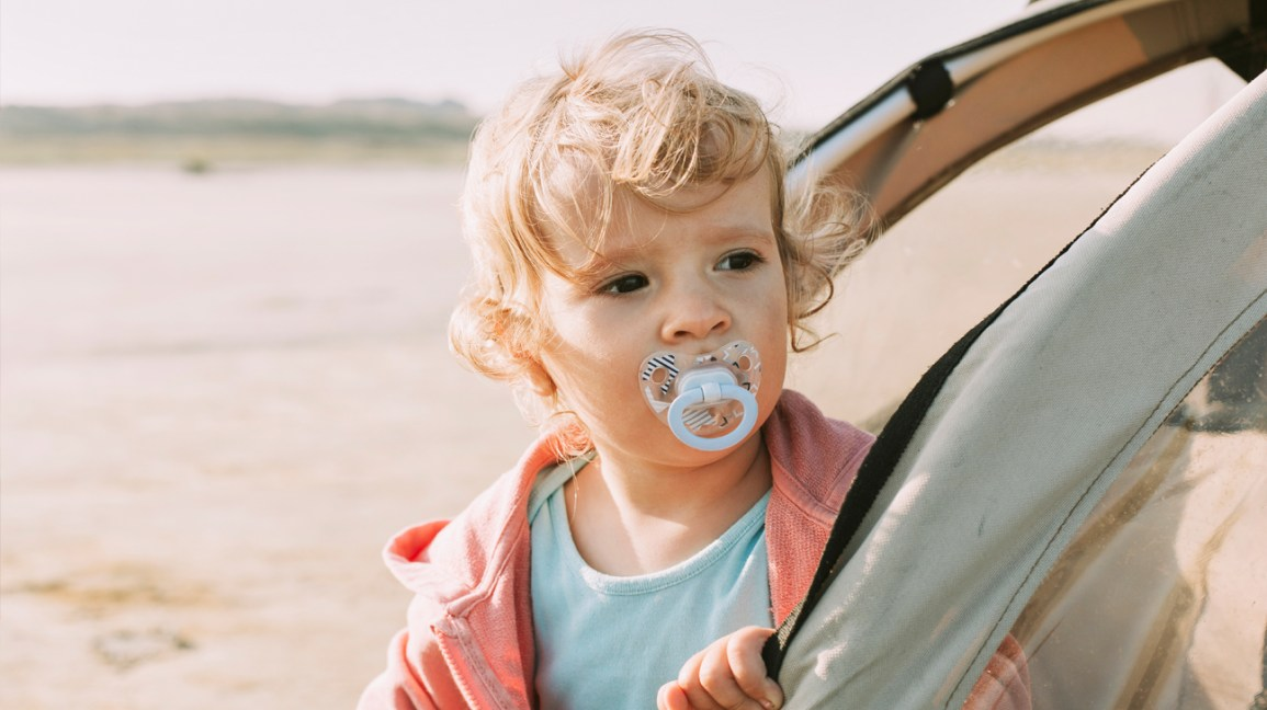 Ağızda emzik ile yürümeye başlayan çocuk