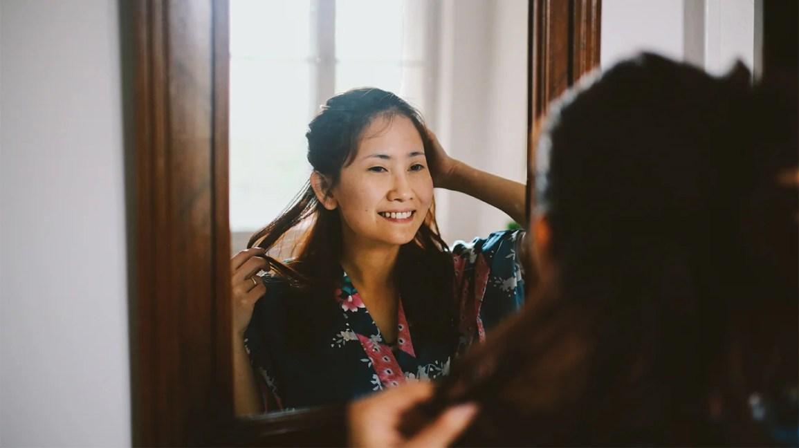 mulher sorrindo olhando seu reflexo no espelho